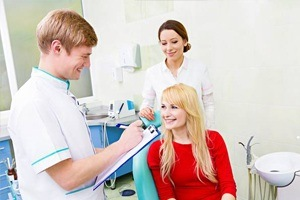Young woman in dental chair talking to dentist