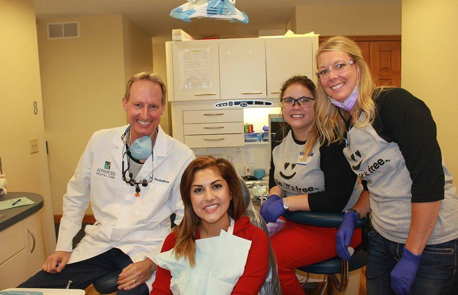 Smiling patient denetist and two team members in treatment room