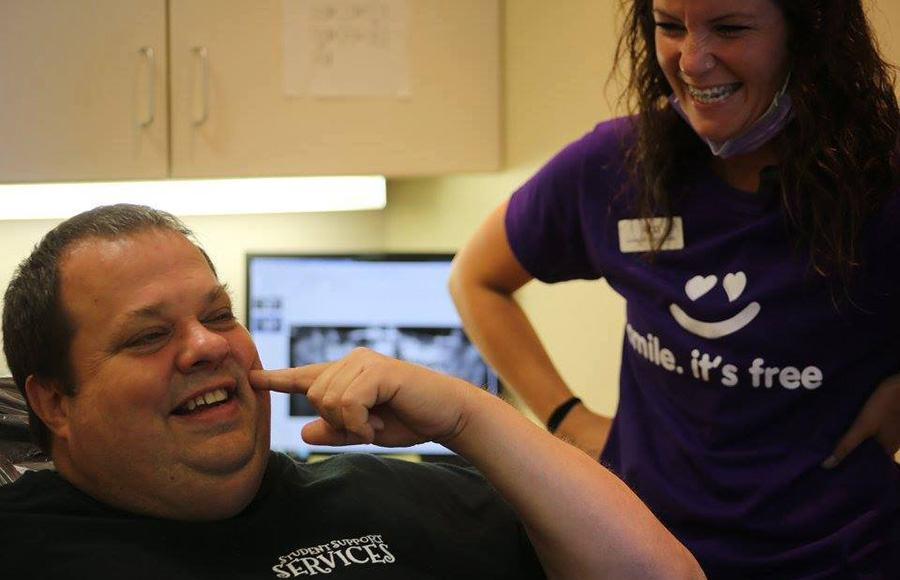 Smiling dental team member and patient pointing to cheek
