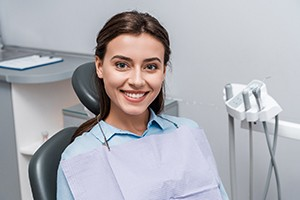 Smiling woman sitting in dental chair with new dental bridge in Springfield, IL