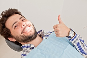 Male patient lying back in chair giving thumbs up