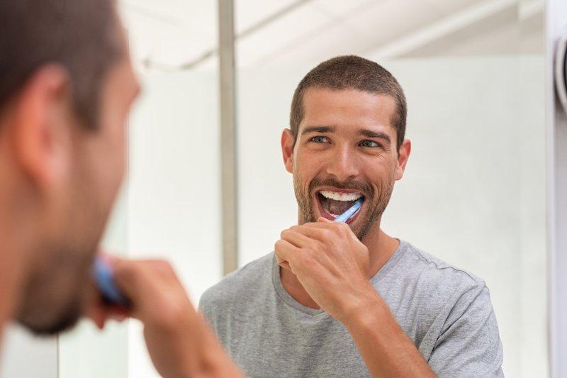 man brushing his teeth in the mirror